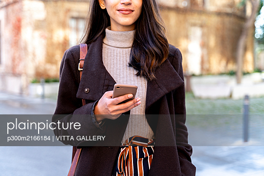 Close-up of woman holding smartphone in the city - p300m2166184 by VITTA GALLERY