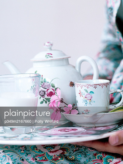 Woman holding chinaware teaset on tray - p349m2167660 by Polly Wreford