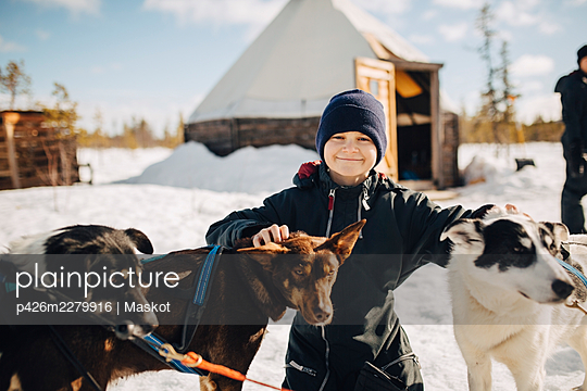 Portrait of boy wearing knit hat stroking husky dogs during winter - p426m2279916 by Maskot