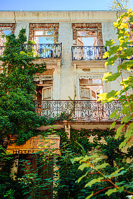 Facade of abandoned hotel - p1053m1462860 by Joern Rynio