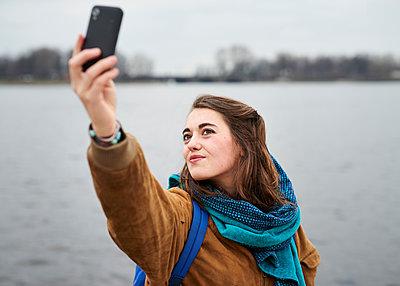 Junge Frau macht Selfie am Wasser - p1124m1123275 von Willing-Holtz
