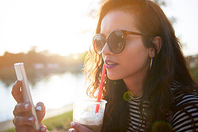 Stylish young woman with cell phone and takeaway drink outdoors at sunset - p300m2012224 von gpointstudio