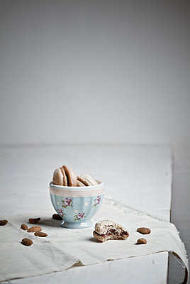 Bowl with macaroons while almonds scattered - p300m2207349 by Susan Brooks-Dammann