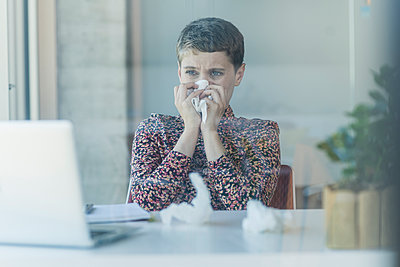 Ill businesswoman at desk in office blowing nose - p300m2214188 by Uwe Umstätter