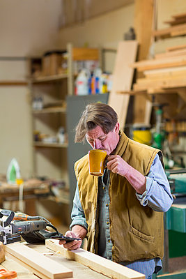 Caucasian carpenter drinking coffee and texting on cell phone in workshop - p555m1301771 by Marc Romanelli