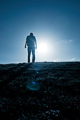Silhouette of man standing on grassy field - p597m2026529 by Tim Robinson