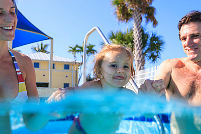 Parents swimming with toddler in pool - p924m768404f by Stuart Westmorland