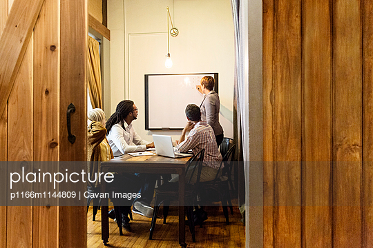 Businesswoman writing on whiteboard in creative office - p1166m1144809 by Cavan Images