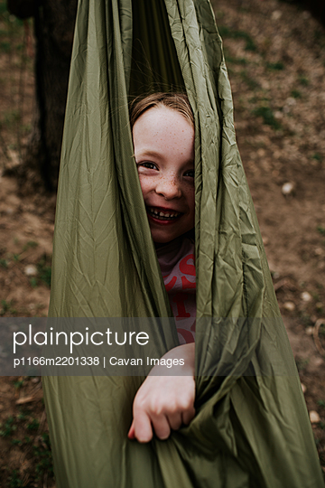 Vertical of young girl wrapped up in hammock outside - p1166m2201338 by Cavan Images