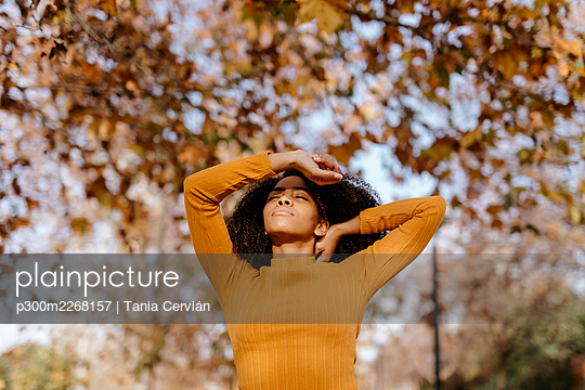 Portrait of African American woman in autumnal park in Granada, Spain. african american woman afro fall park sunlight autumn yellow mustard - p300m2268157 von Tania Cervián