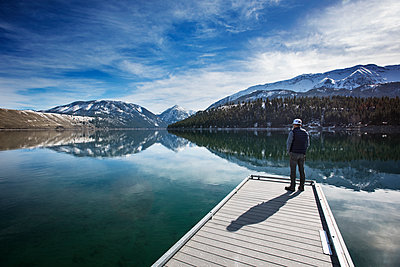 Rear view of man looking at Wallowa Mountains while standing on pier - p1166m1145124 by Cavan Images