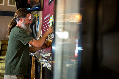 Side view of bartender pouring beer from tap - p1166m1489902 by Cavan Images