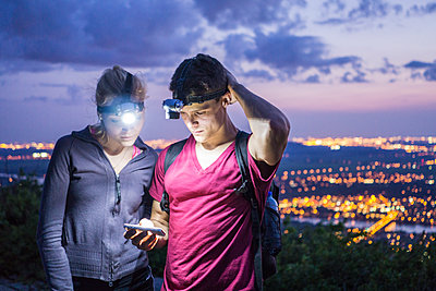 Couple hiking together on mountain peak using mobile phone for d - p1166m2095365 by Cavan Images