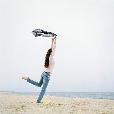 Young woman holding up a scarf on the beach - p3741532 by Karin Smeds