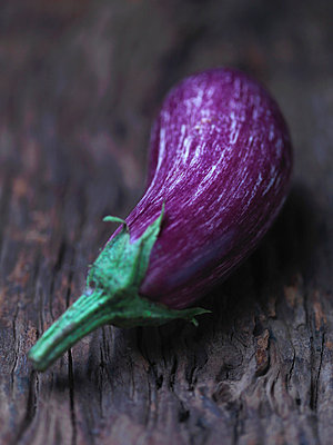Aubergine on wooden counter - p429m757548f by Danielle Wood