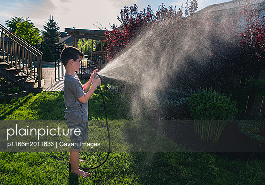 Side view of boy watering plants with garden hose at backyard - p1166m2011833 by Cavan Images