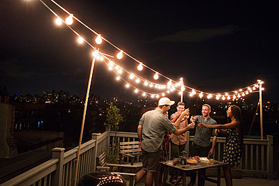 Cheerful friends enjoying drinks on building terrace at party - p1166m1097911f by Cavan Images