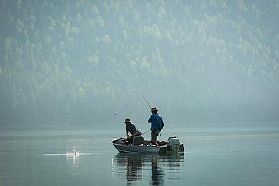 Two fishermen fishing in the river - p1315m2055878 by Wavebreak
