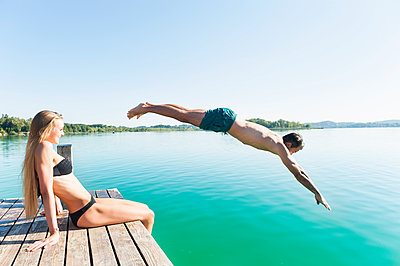 Young man in swimming shorts jumping from jetty into lake while his girlfriend watching him - p300m2198140 by Daniel Ingold