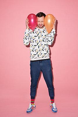 Junger Mann mit zwei Luftballons - p341m1216631 von Mikesch