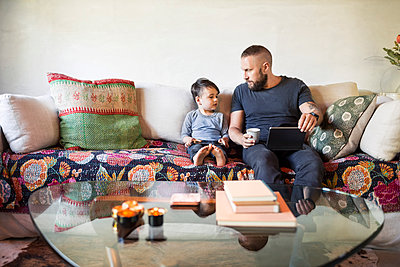 Father and son with digital tablets sitting on sofa at home - p426m1062745f by Maskot
