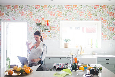 Female blogger using laptop while carrying daughter in kitchen at home - p426m2116976 by Maskot
