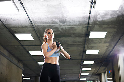 Woman exercising with kettlebell in gym - p429m2019231 by Peter Muller