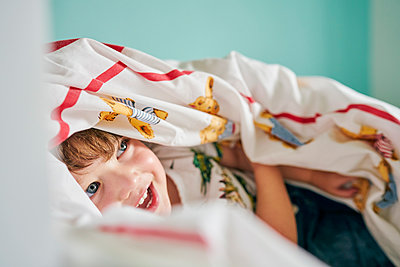 Toddler hiding under blanket in room - p429m2164630 by GS Visuals