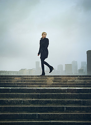 Woman in black coat - p984m2022597 by Mark Owen