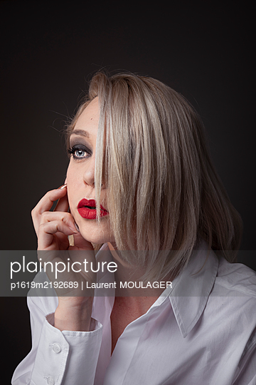 Portrait of a blonde young woman with red lipstick - p1619m2192689 by Laurent MOULAGER
