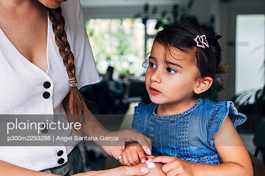 Woman putting adhesive bandage on girl's knee at home - p300m2293288 by Angel Santana Garcia