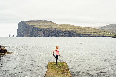 Sportswoman warming up on pier - p1166m2224472 by Cavan Images