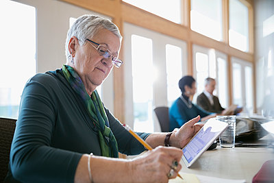 Senior woman using digital tablet taking notes in classroom - p1192m1212929 by Hero Images