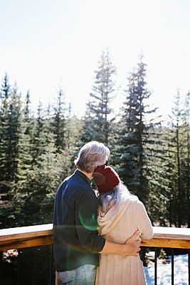 Affectionate couple hugging on sunny balcony overlooking woods - p1192m2094231 by Hero Images