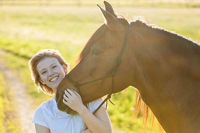 Portrait of happy of young woman with horse at backlight - p300m1460158 by Tom Chance