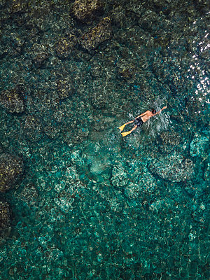 Indonesia, Bali, Man swimming in ocean at Amed beach - p300m2059341 by Konstantin Trubavin