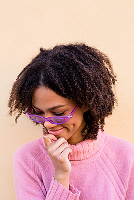 Portrait of smiling young woman wearing pink pullover and purple sunglasses - p300m2070261 von Lucas Ottone