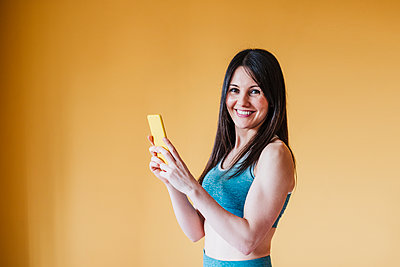 Smiling woman holding smart phone by yellow wall at home - p300m2274196 by Eva Blanco