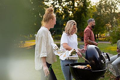 Female friends preparing food on barbecue - p312m2280819 by Plattform