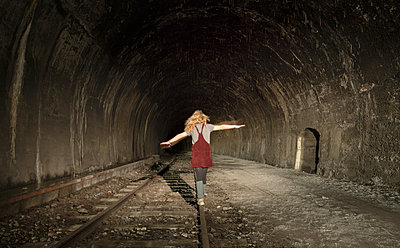 Girl in a deserted railway tunnel, walking along track, rear view - p429m1227298 by Mischa Keijser