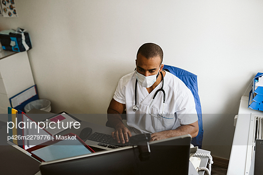Male healthcare worker wearing face mask using computer in medical clinic - p426m2279776 by Maskot