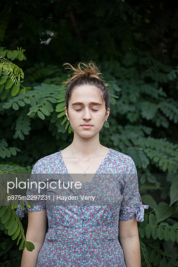Young woman in front of a bush, portrait - p975m2297231 by Hayden Verry