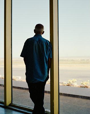 Man looking out on runway - p1118m1553107 by Tarik Yaici