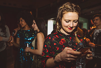 Smiling female millennial texting with smart phone in nightclub - p1192m1567129 by Hero Images