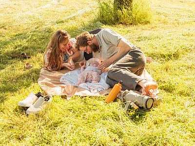 Young couple relaxing with baby girl on blankets on a meadow - p300m2070311 by Albrecht Weißer