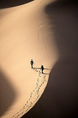 Tourists leaving footprints while walking on sand dune in Sahara Desert - p343m1475894 by David Santiago Garcia