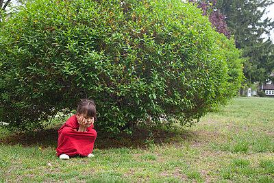 A Little Girl Hiding By Bush - p463m1064532 by Yo Oura