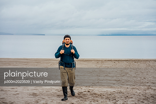Man with backpack, walking on the beach - p300m2023539 von Vasily Pindyurin