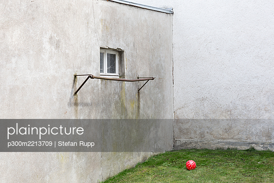 Germany, glum backyard with red ball - p300m2213709 by Stefan Rupp