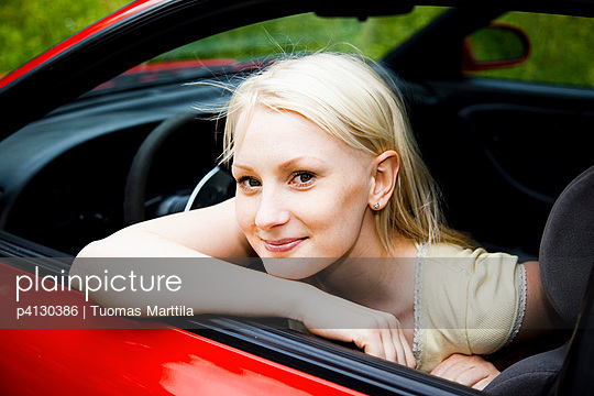Young woman sitting in her car - p4130386 by Tuomas Marttila